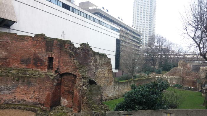 Photo of derelict ancient wall against new white buildings