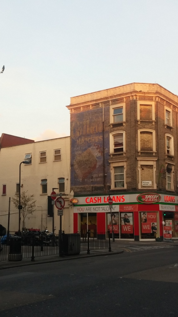 Photo of old building advertising above a shop